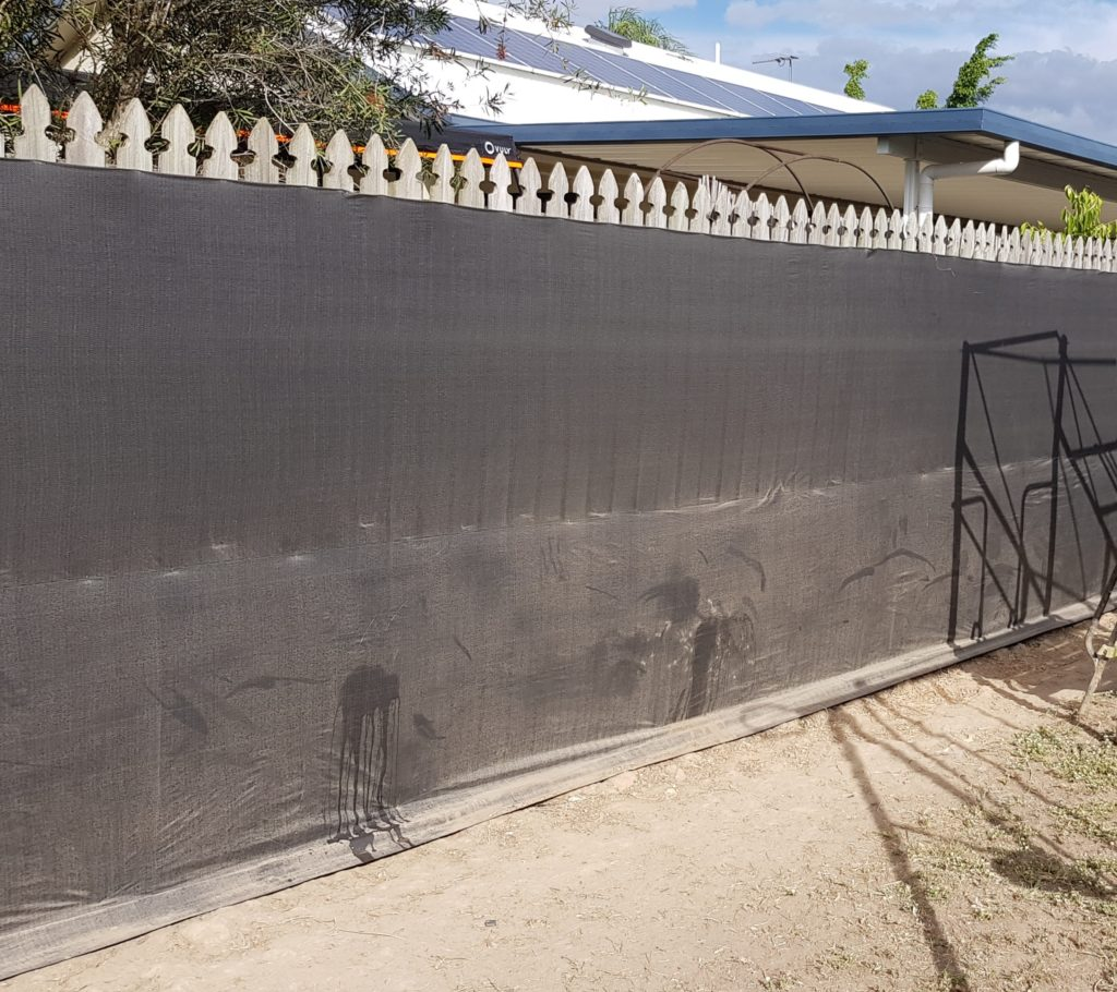 Black tarp fixed to a wooden fence